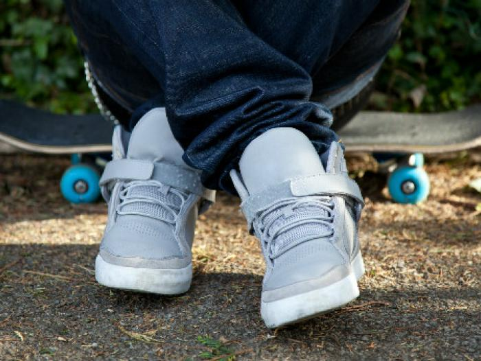 Best-Skate-Shoes-skater-sitting-on-skateboard-showing-upper-part-of-skateboarding-shoes