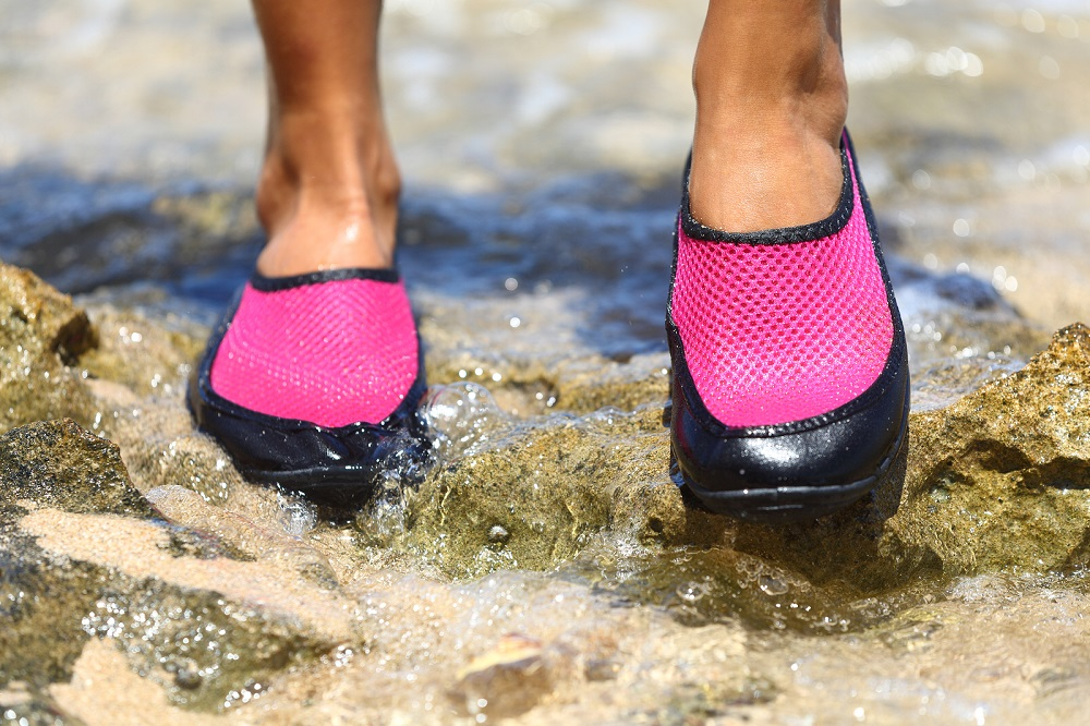 Best-Water-Shoes-girl-in-pink-shoes-standing-on-wet-rock-in-water