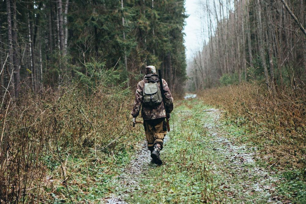 Best Hunting Shoes-Hunter on a trail with gun