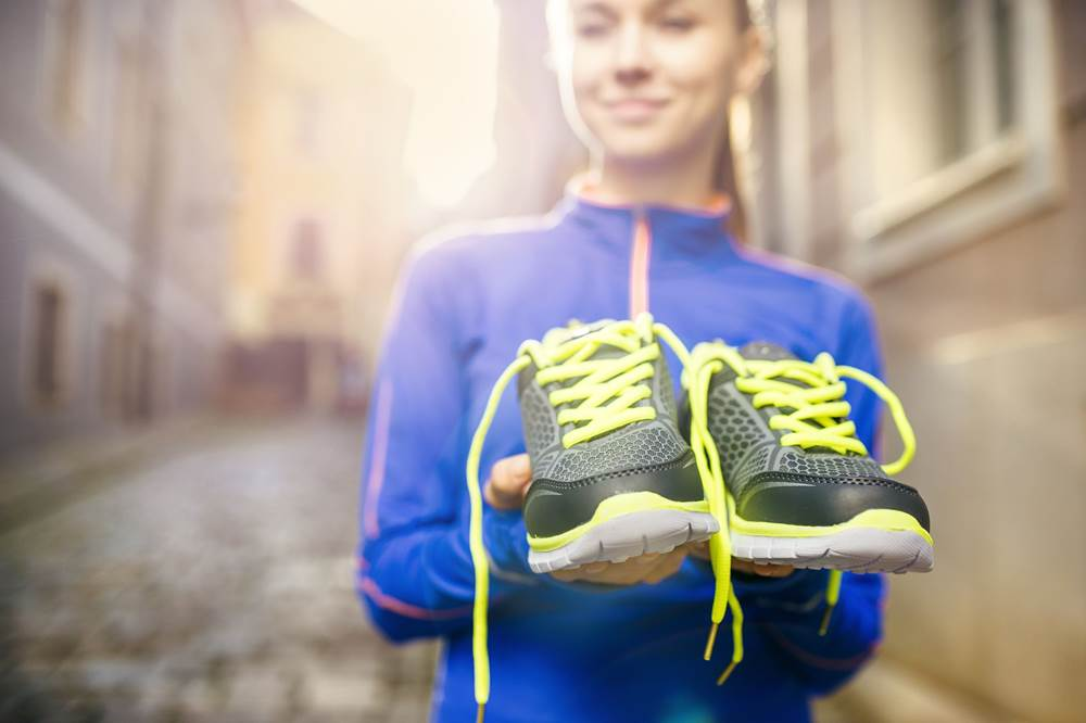 best running shoes girl-runner-carrying-her-running-shoes