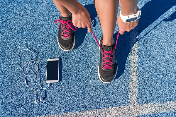 best-running-shoes-runner-tying-shoes-on-a-track