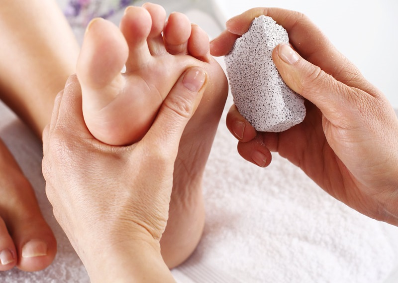 Foot Callus & Corn Removal-man removing calluses on womans foot