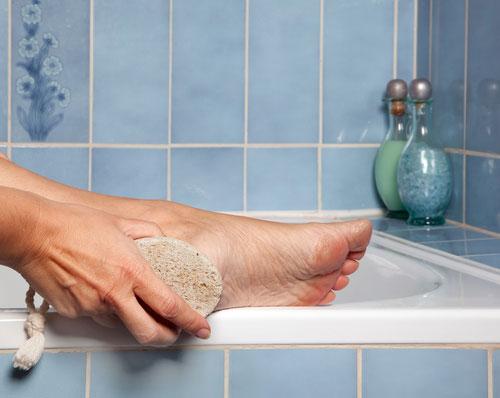 Foot Callus & Corn Removal-woman scrubbing calluses